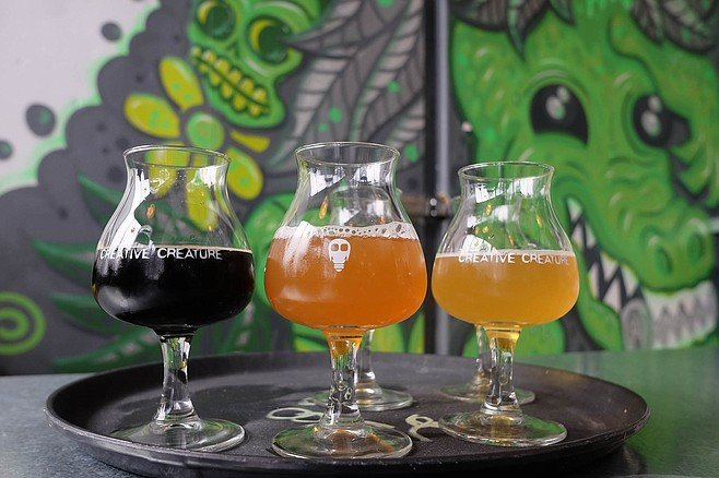 A flight of beers overseen by grinning monsters and skulls at Creative Creature brewing