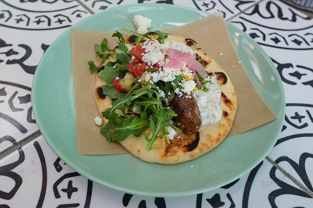 A merguez lamb sausage taco, served on a grilled pita