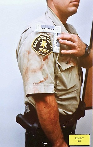 Deputy Elmone with dog blood on his uniform, after he carried Banjer away.