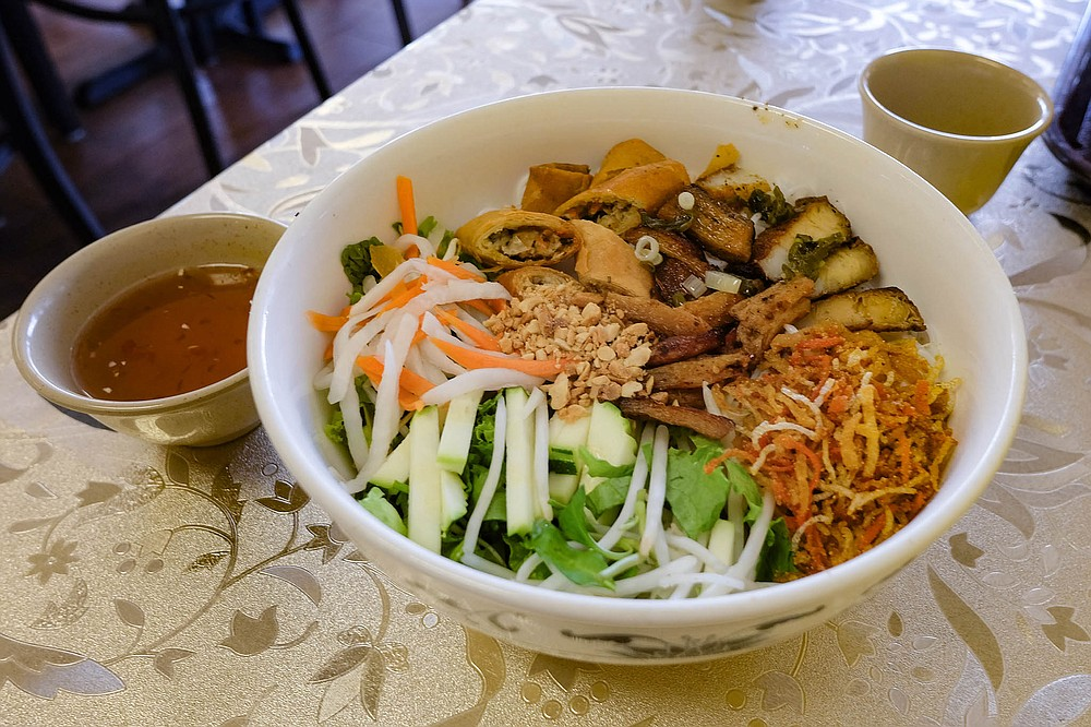 Cold vermicelli noodles topped with a mix of vegetables, faux meats, crushed peanuts, and chopped egg rolls