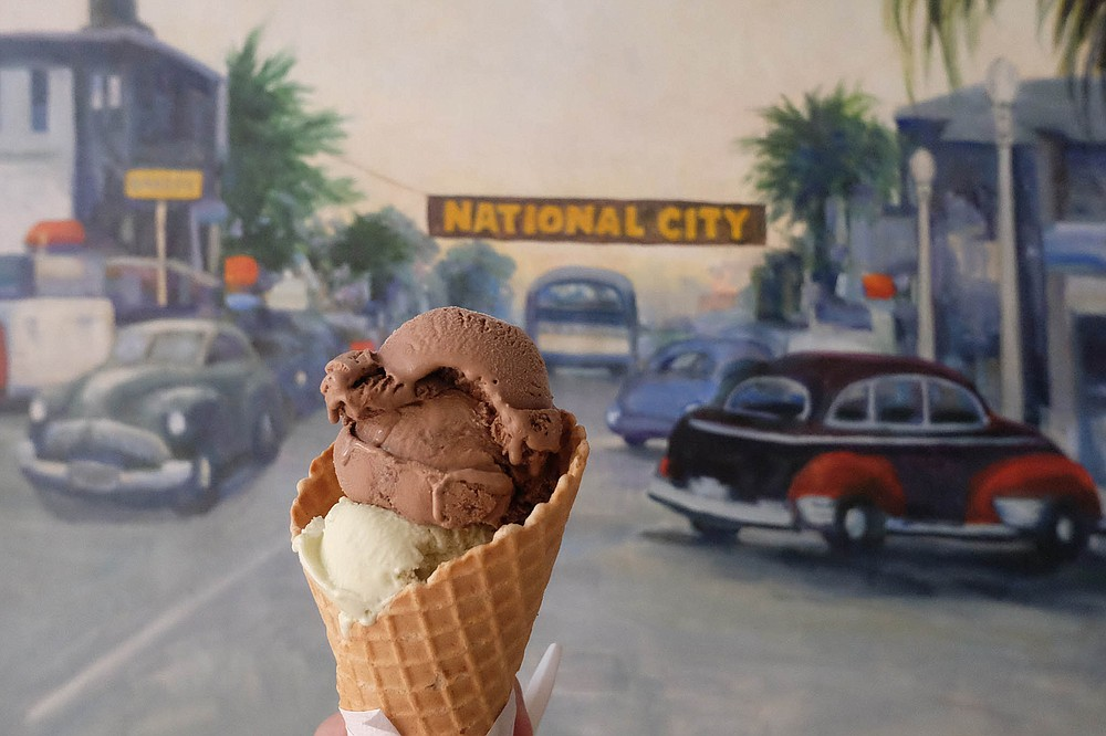 A cone filled with avocado and red ale Mexican chocolate ice cream, in front of a National City mural inside Niederfrank's Ice Cream