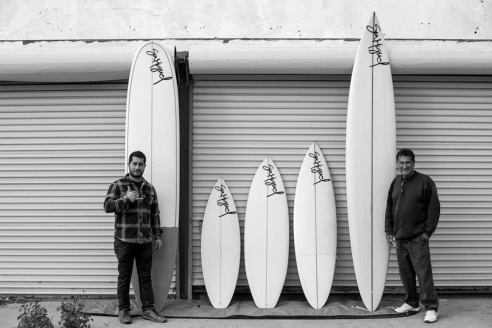 Chega and his son, Chega Jr. with a quiver of the surfboards.
