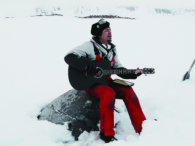 Pablo Cantua sings in Antarctica. Audience of penguins behind him.