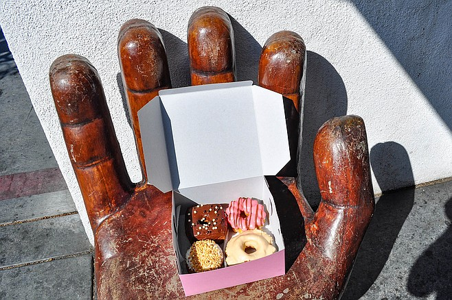 A hand-shaped chair holds a box of donuts at Peterson's Donut Corner.