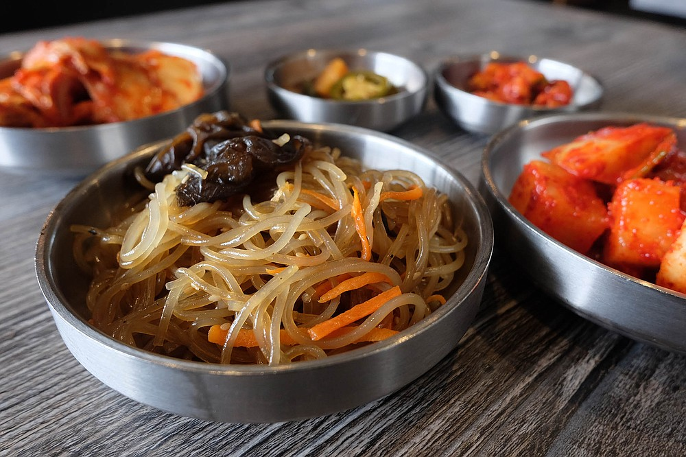 Sesame noodles, spicy daikon, and kimchi are part of Woomiok's banchan package.