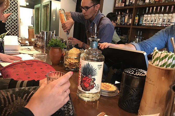 Tequilas and mezcals pouring out during frantic Friday happy hour