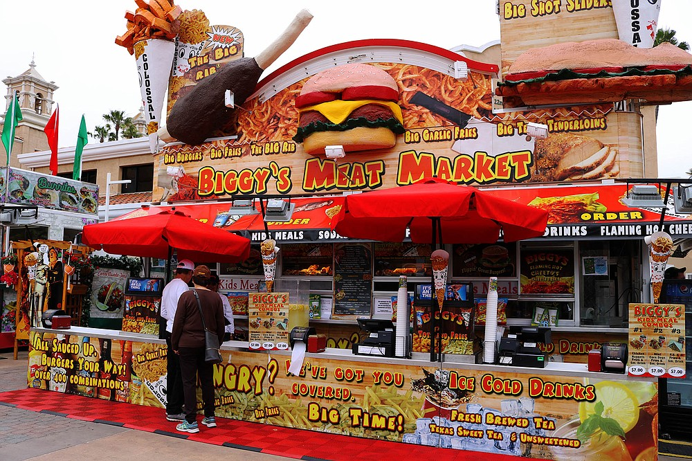 Like most fair vendors, Biggy's Meat Market uses loud photos and giant food models to attract attention