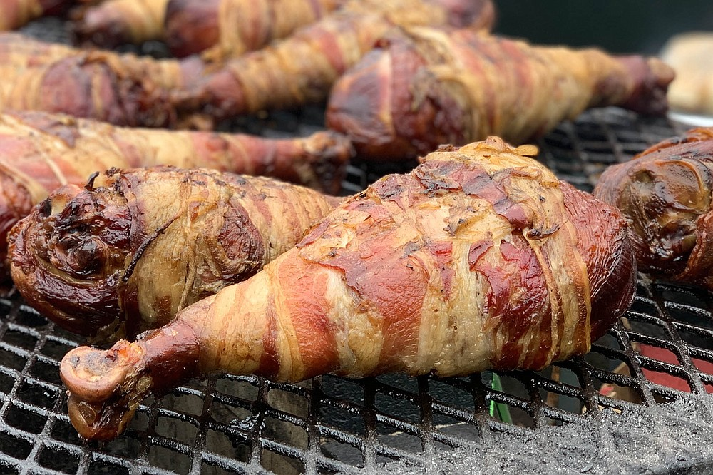 Bacon wrapped turkey legs cook on a grill at the fair.