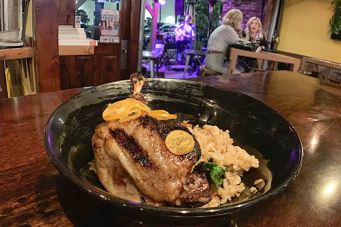 Duck confit over rice while a musician plays and bar customers mingle