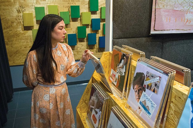 """Erika Katayama, the exhibit's curator, flips through secrets encased in vinyl album covers. """"It's like being in a record store again."""""""