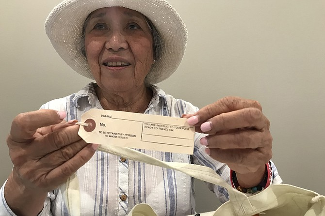 Eileen Oya holds I/D tag like the one she and her family had to wear when they were transported to internment camp in Arizona in 1942