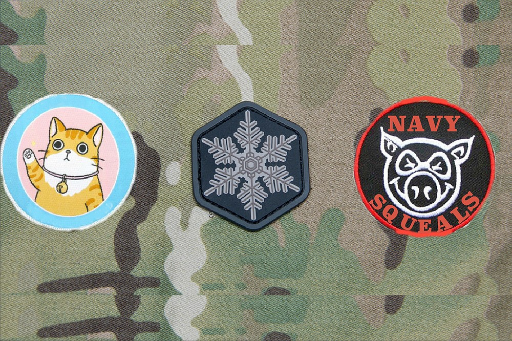 """From left to right: The """"Bunch of Pussies"""" patch, so called because, according to a letter provided to the Navy Times, Gallagher responded to criticism that it was extremely unnecessary to train troops by placing them in daytime live-fire situations by saying that his junior SEALs — several of whom testified against Gallagher — were """"all a bunch of pussies"""" who needed the kind of engagement where """"you need to focus on your field of fire or else you could take (a bullet) to the side of the head."""" (The pussy in question notably wears a bell around its neck, much like the cat in the Aesop's Fable, which serves to warn of its approach. This is taken as a reference to Gallagher's decision to, as prosecutors put it, """"spread rumors about his teammates to members of the SEAL community, describing them as cowards who were afraid to go out on missions,"""" even going so far as to """"tell the new chain of command for teammates who had transferred."""" Gallagher's attorney did not deny the accusation, but preferred to call it """"telling the truth."""") Second is the Snowflake patch, with its obvious designation of the young SEALs as members of the overly-emotional, easily offended, conflict-averse Generation Snowflake. (""""This all started because these kiddies thought I was stealing from their care packages, and they get grumpy when they don't get their afternoon milk and cookies,"""" Gallagher has been reported as saying. """"So they ganged up and formed the military equivalent of an online mob and tried to cancel me. But the Navy isn't Twitter, thank God."""") Finally, the Navy SQUEALs patch, wherein SQUEAL stands for Sissified Quisling Unable to Endure Actual Leadership. Because, as Gallagher's attorneys put it, """"Those little piggies tried to go wee, wee, wee all the way home, but the Big Bad Wolf was too smart for them."""" A fourth patch, depicting a bulls-eye target and intended to be worn on the helmet, was considered but ultimately rejected. After all, said Gallagher, """"We're a brotherhood."""""""