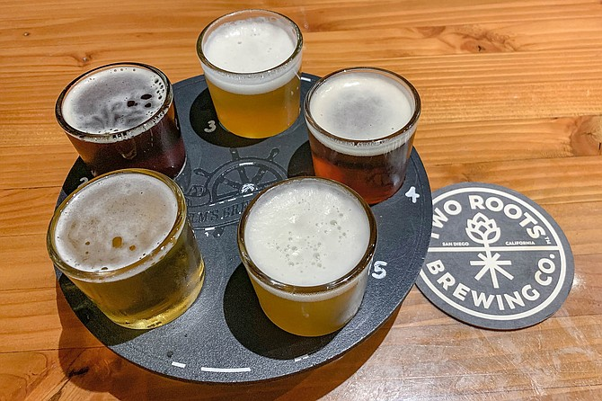 The Helm's Brewing logo has been scraped of this Two Roots flight tray.