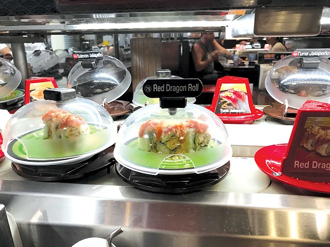 Each plate at Kura Revolving Sushi Bar only costs $2.60, and before you know it, you've had a dozen of these things.