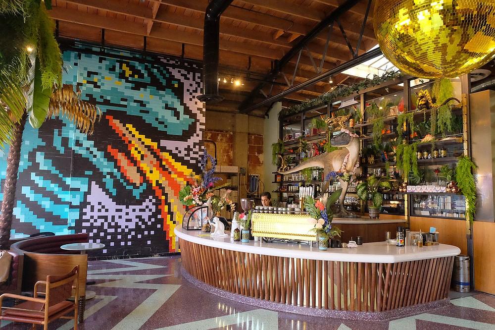 Godzilla and a velociraptor create a unique coffee shop experience.