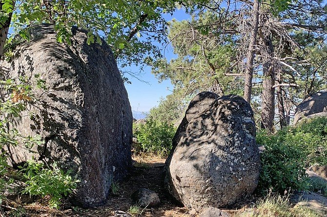 The trail passes between two large boulders at the top of the hill