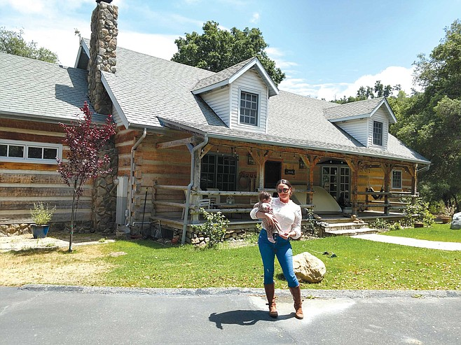 Angela Acosta stands in front of a Warner Springs home built in 1989 by Roger Craig, a World Series-winning baseball player
