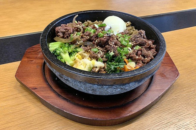 Hot stone bowl of seaweed rice, mixed vegetables, bulgogi beef, and a sous vide egg