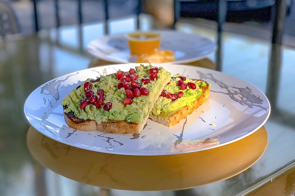 Pomegranate seeds find a place on avocado toast (ginger-turmeric wellness shot added for good measure).