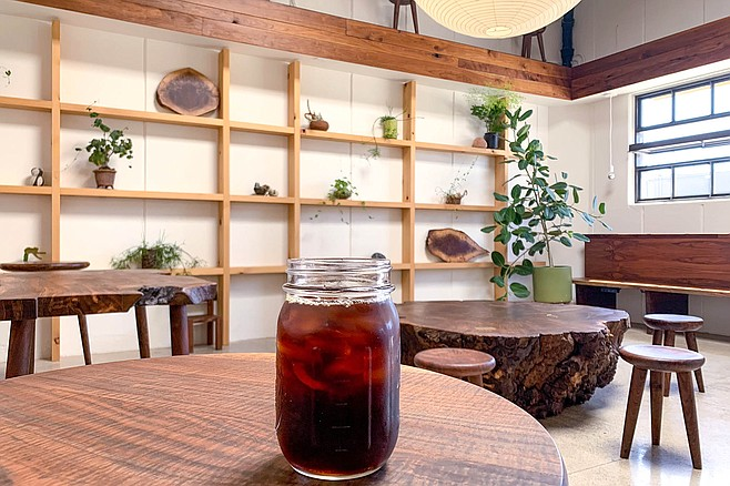 A jar of cold brew coffee in a lounge of specialty wood furnishings