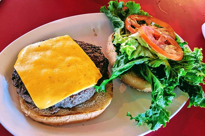 "1/2-pound Boll Weevil Steerburger with cheese, toasted bun, lettuce, and tomato. A giant condiment tray on the table allows costumers to customize with red onion, pickles, yellow chili peppers, and all the sauces including their ""secret sauce,"" which I've loved since my childhood."