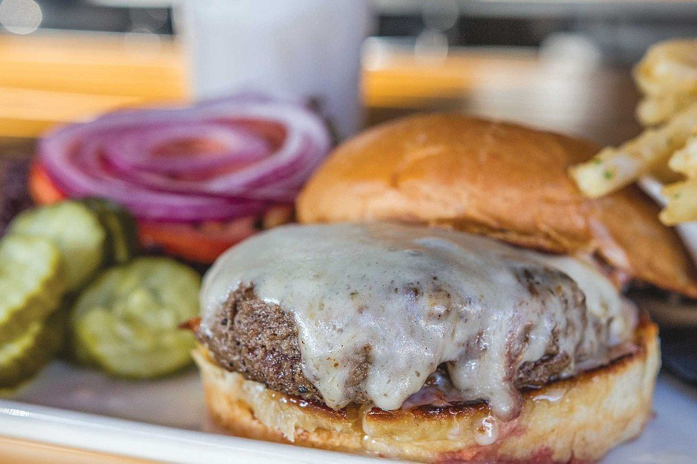 The Masters Burger sees a half pound of angus beef topped with melted, aged white cheddar and served on a lightly toasted potato bun with bacon aioli spread, and veggies on the side.