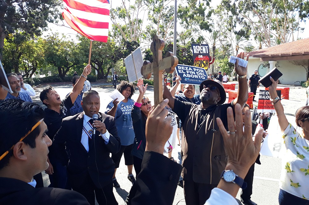 Protest leaders Ruben Serrano (with cross), Andres Wong (flag), Tony Villafranca (microphone), and Pastor Dennis Hodges (hands up) pray outside the Civic Center Chula Vista Public Library.