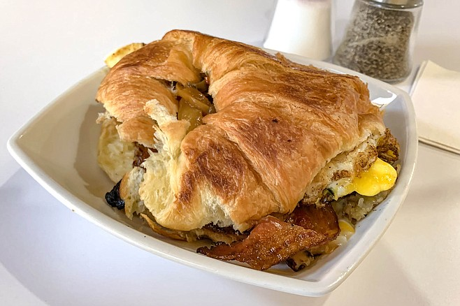 The All American brings together bacon, eggs, potatoes, and a croissant.