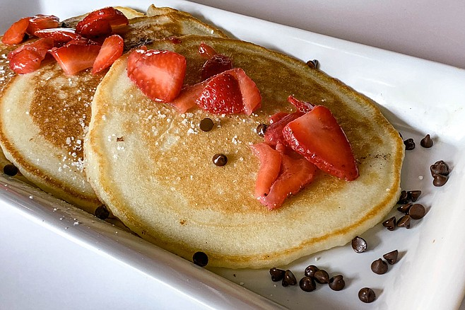 Basic B. pancakes topped with strawberries and chocolate chips