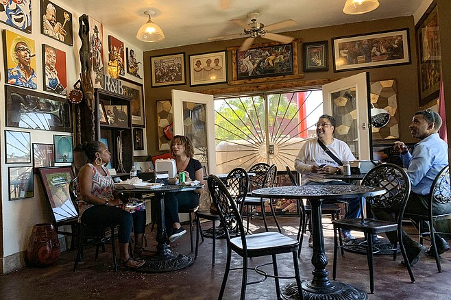 Patrons engage with the owners in one of the art- and music-infused dining rooms at Bowlegged BBQ.