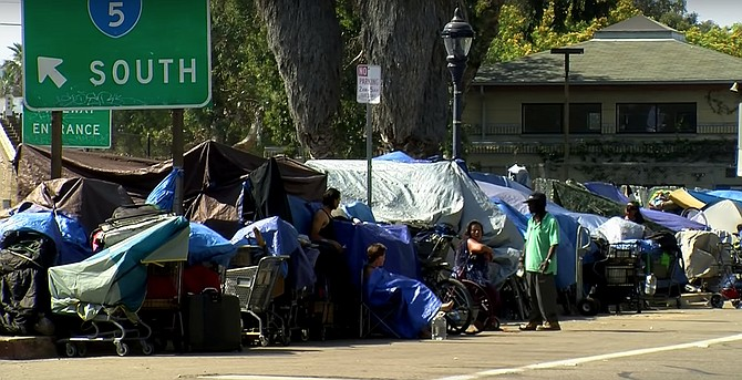 """""""President Trump said during his visit that he wants to 'help' the homeless in California by tearing down their tents and moving them into government housing,"""" said Homeless Advocate James Hardknox. """"And it's true that there are those of us who have been agitating for increased government assistance in finding homes for these people. But when Donald Trump offers to help, it should be enough to give any decent person pause. And after pausing, I realized that Janis Joplin sang it best: 'Freedom's just another word for nothing left to lose.' Which means that when you've got nothing left to lose, you're truly free. And freedom is what America is all about. How dare Trump try to deny these people their freedom by taking away their chosen lifestyle and forcing them to live in some square - and I do mean square - building? And now Imperial Beach is prohibiting people from sleeping on city property, including sidewalks. Sleeping, like skateboarding, is not a crime!"""""""