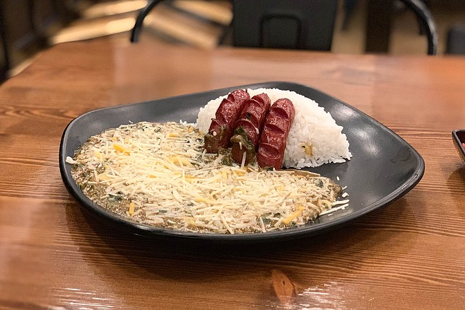 Spinach curry covered in grated cheese, with kurobata sausage