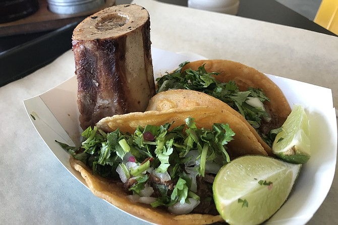 The upstanding beef bone is impressive, but the birria tacos hold the golden prize here