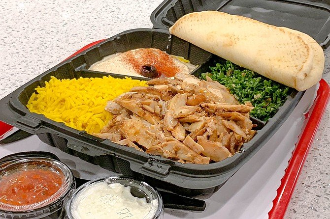 A chicken shawarma plate, served with house sauces and hummus