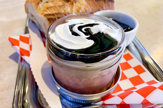 Chicken pâté served in a jar with schmaltz and balsamic reduction