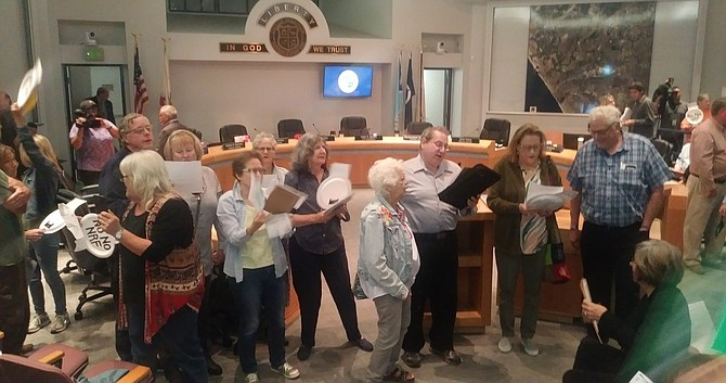 "Larry Kornit (center, white shirt) and other Oceanside locals use Beatles tune with an anti-North River Farms chorus ""Can't buy our vote""  at November 6 city council meeting."
