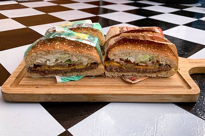 Split in half, we can see minor differences between patties on these Whoppers with cheese.