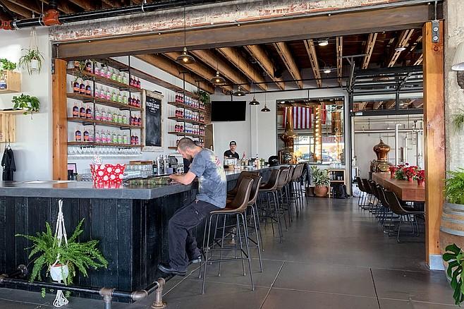 Copper stills visible behind the bar and restaurant at Pacific Coast Spirits