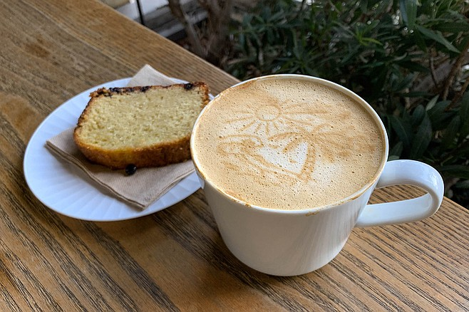 A beach scene printed on a mug of latte, alongside a pastry from Bali Coffee