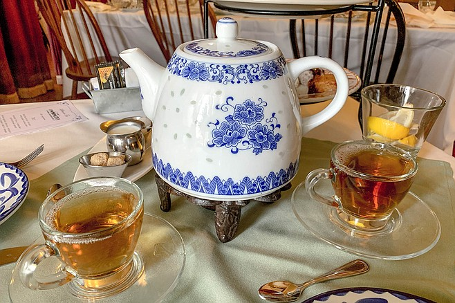 Cups of assam tea poured from a traditional blue and white floral teapot