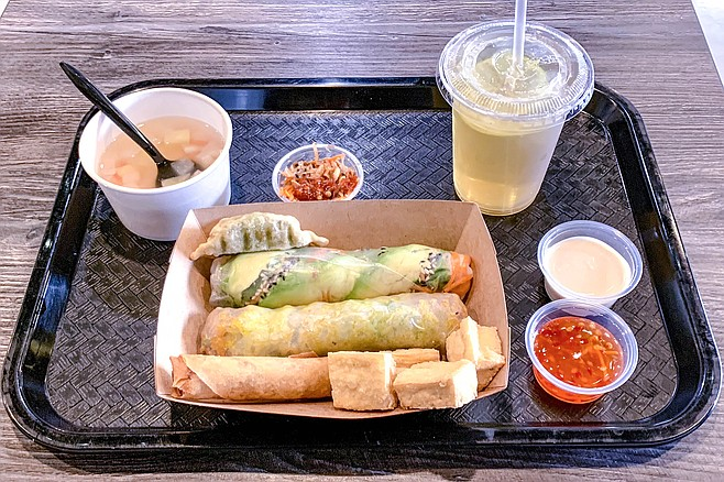 The vegan combo #4: egg roll, crispy tofu, dumpling, soup, tea, vegan crepes roll, and spring roll with avocado, pickled carrot, and sesame seeds