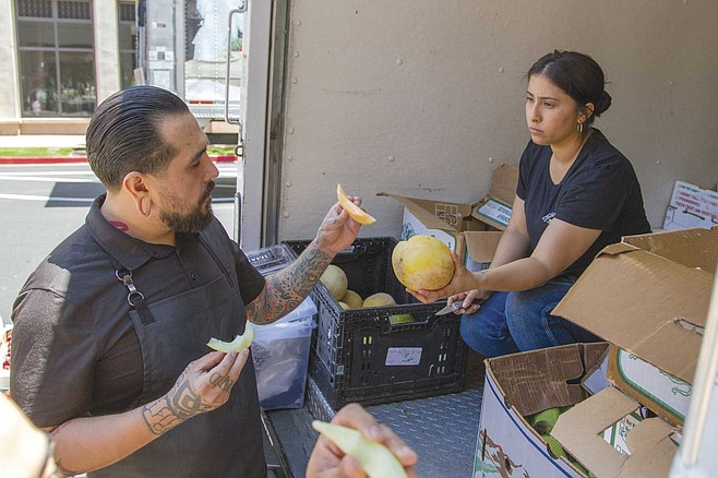 Ashley Bonilla, a rep for Specialty Produce who also happens to be JoJo Ruiz's fiancée, cuts slices from heirloom fruits, and hands everyone pieces to sample.