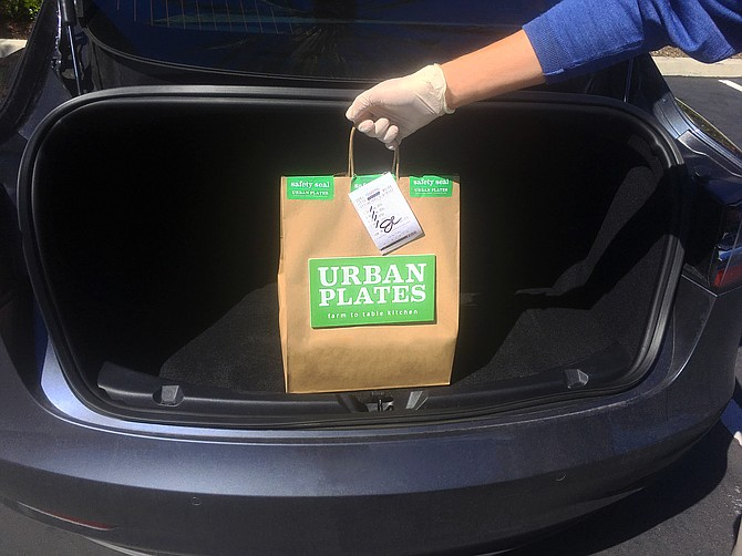 An Urban Plates meal, dropped into a car trunk, curbside, for no contact pick-up