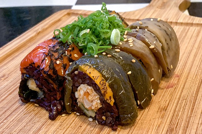 """The """"neon gravestones"""" roll, made with black rice, vegan """"shrimp"""" and """"tuna"""", and cucumber, topped with scorched peppers and eggplant"""
