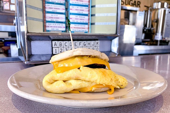 House spicy sausage patty and omelet with American cheese slices, on an English muffin