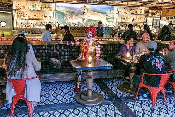 A satirical Ronald McDonald statue buffers socially distanced parties at Craft & Commerce.