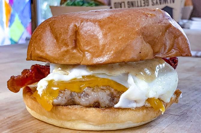 A breakfast sandwich bigger than a double double, with bacon, sausage, fried egg, and cheddar on brioche bun.