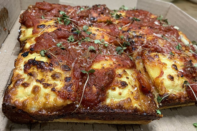 The rectangular, Detroit style pizza, topped by cheese ravioli and meat sauce