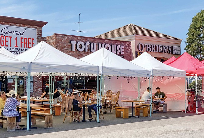 Tofu House couldn't invest more than five grand to build its outdoor venue. It set up tents and Edison bulb strings, and moved its stone pot scorched tables outside.