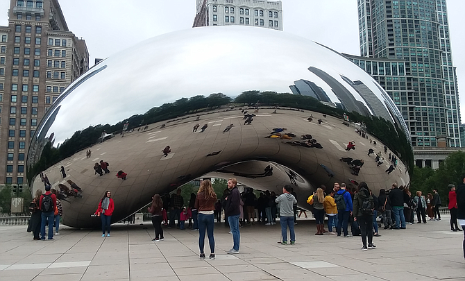 "Commonly known as ""The Bean"", the Cloud Gate sculpture is a popular draw in downtown Chicago's Millenium Park."